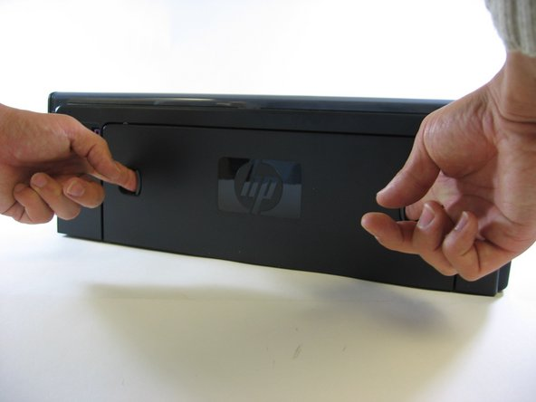 To begin disassembly, locate the two grooves on the back panel of your printer. Next, use two fingers to simultaneously press the grooves DOWN and IN. This step will release the back panel from the printer and allow you to PULL the panel out.