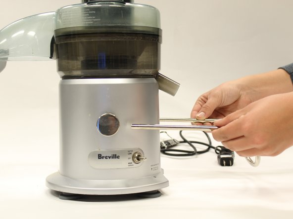 Remove the safety locking arm by gripping both sides and pulling horizontally away from the juicer.