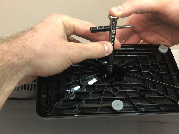 Use a Phillips #2 screwdriver to take out the four screws on the bottom of the base.