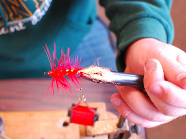 Image 1/2: Next, put your hackle on. Strip the bottom of the hackle feather so it's just the middle part of the feather.