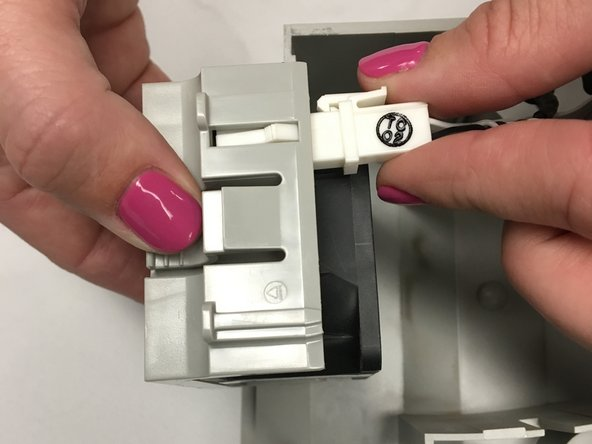 Disconnect the fan by pinching the latch on the connector and pulling straight out. Be sure to pull on the plastic connector, and not on the wire.