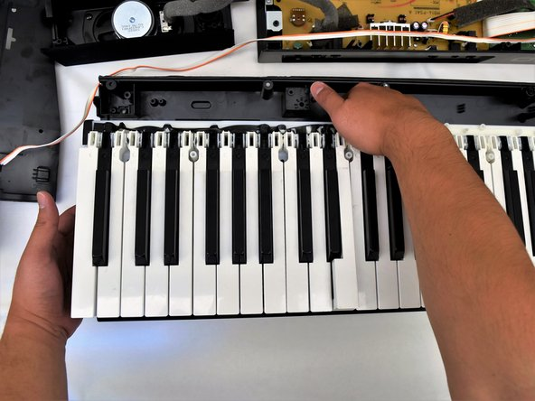 Place one hand on the side with fingers underneath the keys and one hand on the upper edge and lift off of the back panel.