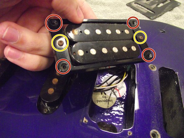 "Using the Phillips 2 Screwdriver, remove the four 9/16"" frame screws from the plastic humbucker frame."