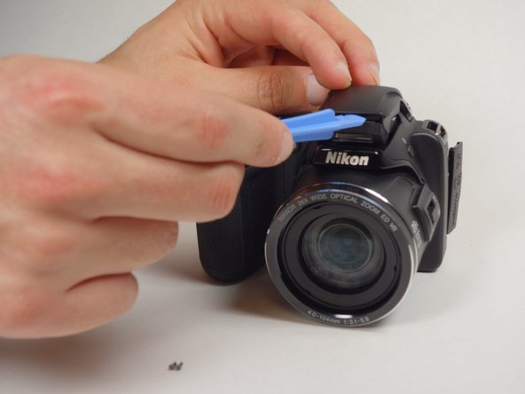 Use blue plastic opening tool to pry open the casing for the flash.
