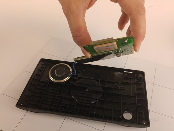Carefully pick up and remove the main circuit board from the device's plastic casing.