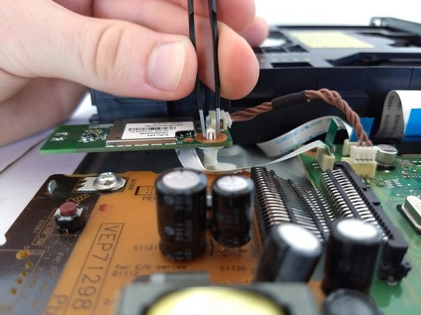Using tweezer, compress the white knob holding the wifi module board in place.