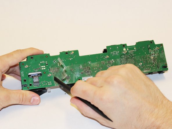 Peel away the plastic film from the motherboard using the spudger.