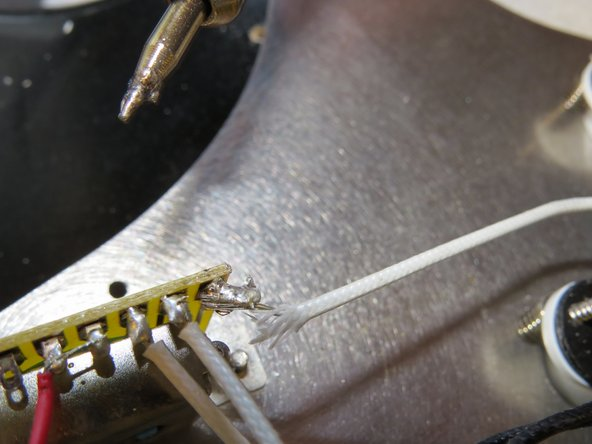 Image 1/3: Gently pull on the pickup wire while melting the solder.