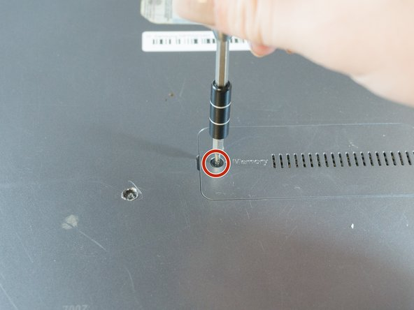Using the Phillips #00 screwdriver, remove the 6.6mm screw from the memory slot cover.