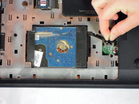 Image 1/2: Using the black tab on the connect and/or a prying tool, lift up to disconnect the black hard drive cable from the green circuit board.