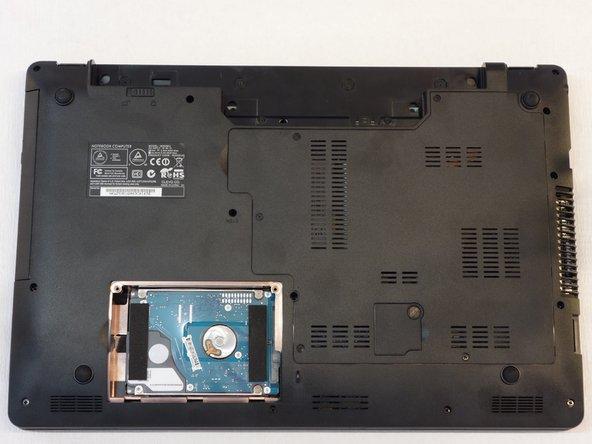 Saisir la languette transparente pour débrancher le disque du connecteur SATA.