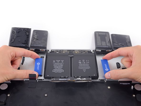 With one plastic card underneath each of the two center battery cells, twist and lift both cards to fully separate the battery cells, together with the plastic frame and battery board, from the MacBook Pro.