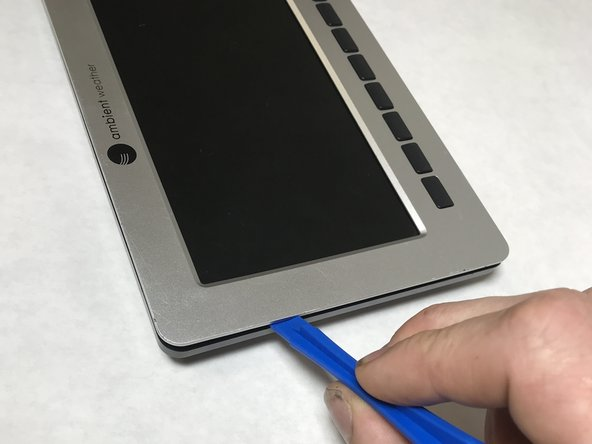 Pry  the front silver panel away from the back black panel with a plastic opening tool.