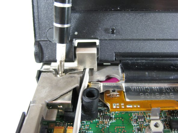 Image 1/1: Remove screw holding the left hinge at the top of the computer.