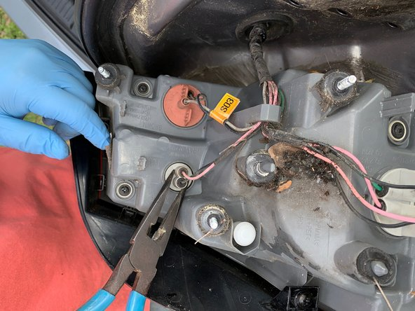 In order to remove the main brake/tail light, remove small light first. This is the same process for the main light. Using pliers grip the plastic and pull while rotating counterclockwise 30 degrees and remove the bulb from the socket.