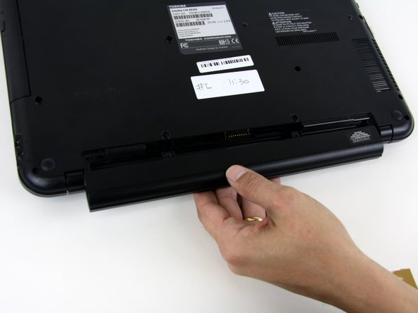 Pull the battery from the back of the laptop for removal from the laptop.