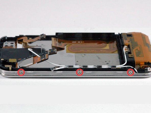 Drehe das iPhone um 90° und entferne die drei Kreuzschlitzschrauben #00 von der Seite des iPhones.
