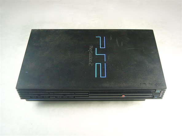 Flip the Playstation 2 (PS2) so that the bottom of the device is facing up.