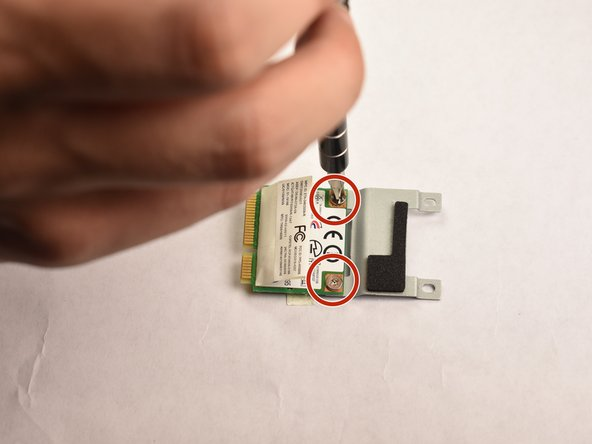 Flip the wireless card over and unscrew the two screws shown in the picture, detaching the wireless card from the plate.