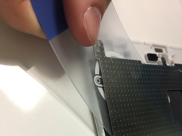 Use the plastic card to separate the metal panel from the screen component.