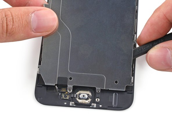 Slide the point of a spudger behind the shield plate to gently lift the home button cable up off of the front panel.