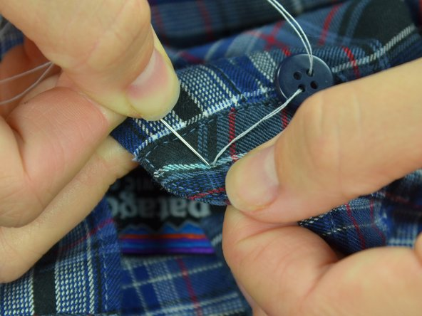 Image 1/3: Pull the thread taut, until the button lays flat on the fabric.