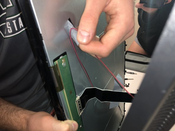 There are wires still keeping the two sides of TV together, so remove all the pieces of tape to detach the wires from sides.