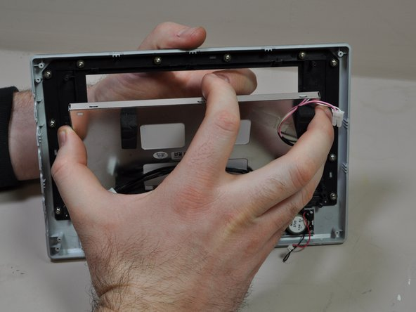 Pivot the screen downward to disengage the remaining clips and lift the screen from the front bezel.