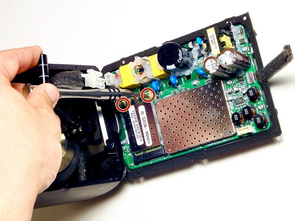 Remove the two 6 mm Torx #6 screws securing the communications board to the motherboard.