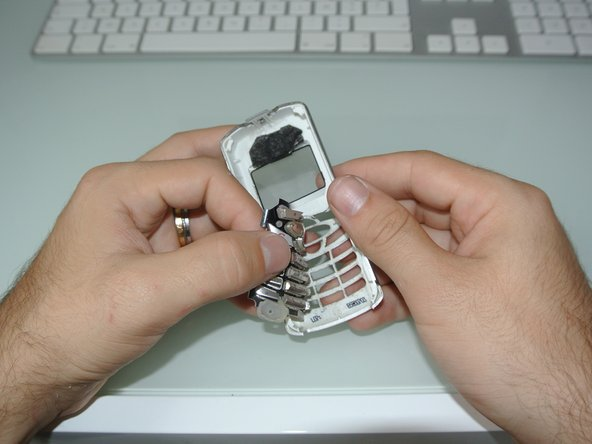 Use your thumb to gently peel the keyboard off the front case.