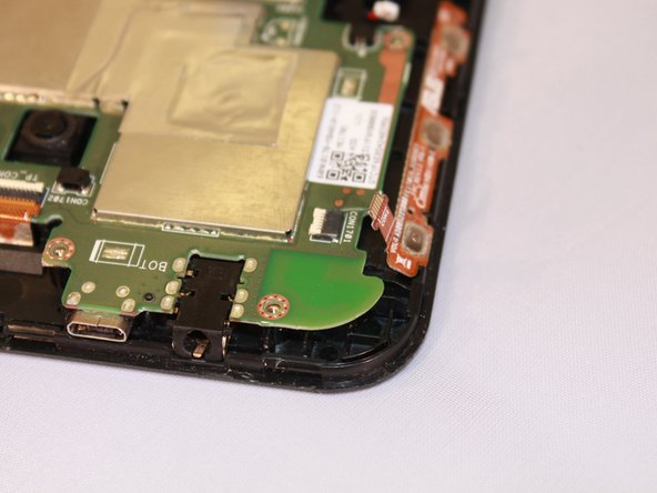 Image 3/3: Using wide nosed tweezers, gently pull out the orange/copper ribbon inserted in the port on the motherboard.