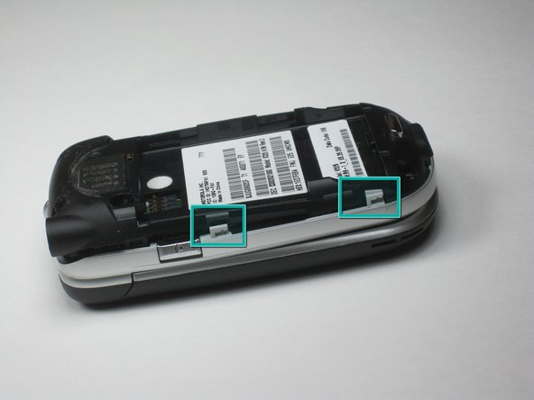 Image 1/3: Using your finger nail or a flat head screwdriver, pull the gray tab away from the body while simultaneously lifting upward on the black rear panel.