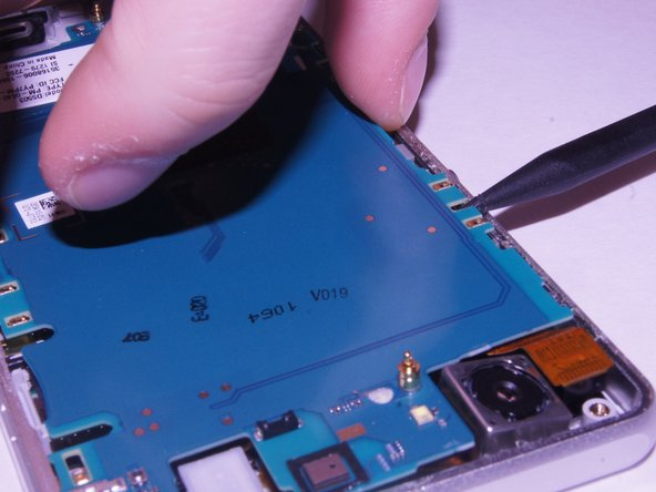Carefully pry up on the four sides of the motherboard using the plastic spudger til it separates from the base of the phone.