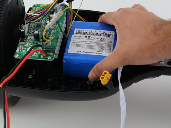 Remove the battery by grasping the battery and hoverboard firmly and pulling apart.