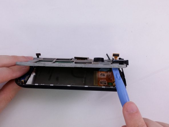 Image 2/3: Using a spudger pry up to create opening to insert plastic opening tool.