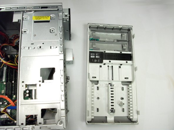 Image 1/1: Remove the CD/DVD drive by pulling it forward towards the front.