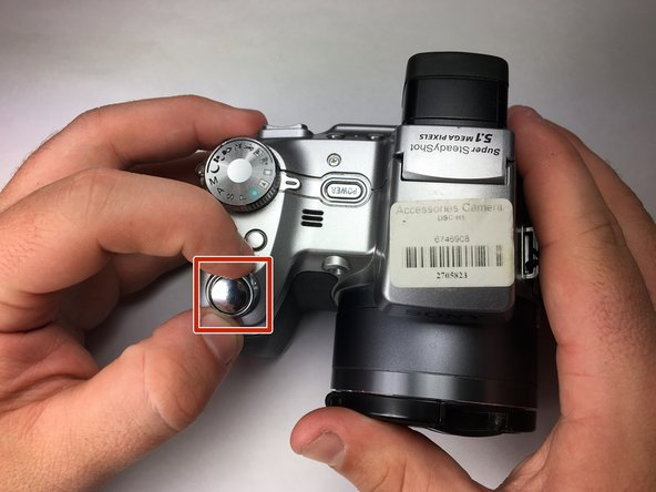 Use a spudger to get a grip on the shutter button and twist clockwise.