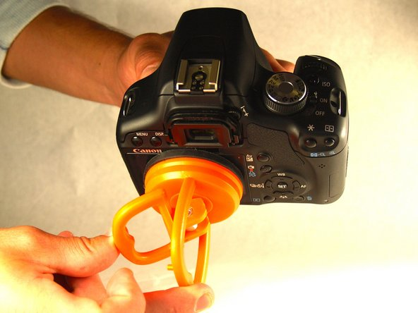 While holding the suction cup flat against the camera screen, suction the two together by pinching the orange handles to meet at the center.