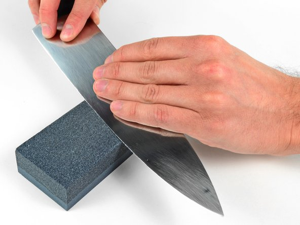 While applying light pressure, push the blade forward along the face of the stone.