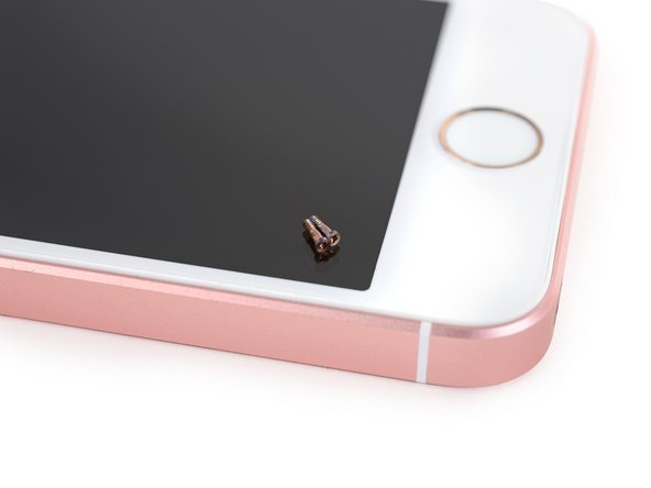 Image 2/3: Setting the pretty pink screws aside, we [https://www.ifixit.com/Store/Tools/iSclack/IF145-243|iSclack|new_window=true] the top off—and there's no pesky, color-matching display adhesive in sight. Compared to Apple's [https://www.ifixit.com/Teardown/iPhone+6s+Teardown/48170#s107852|S-series|new_window=true] [https://www.ifixit.com/Teardown/iPhone+6s+Plus+Teardown/48171#s107891|flagships|new_window=true], this opening procedure is a snap.