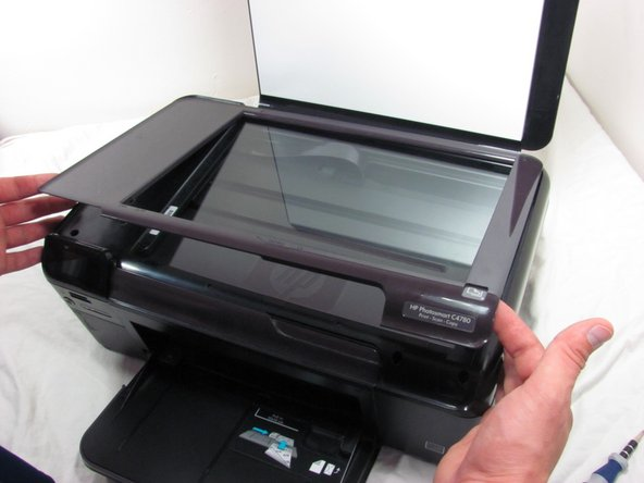 Carefully, pry the plastic frame surrounding the glass away from the printer hood using a plastic prying tool.