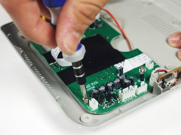 Image 2/3: Place the plastic opening tool underneath the circuit board, and lift up genttly. As you lift up, slide the circuitboard in a direction away from the AVI ports.