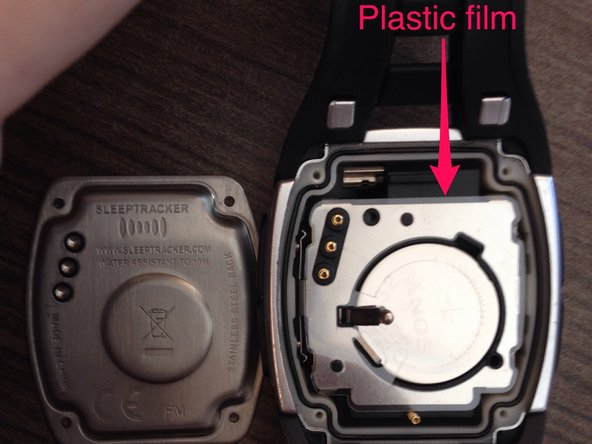 Image 1/2: Underneath, you'll see a sheet of plastic film. It should be possible to remove the battery without removing the film, if you're careful, but I didn't want to risk bending or tearing the plastic.