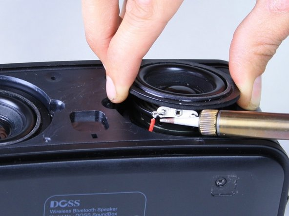 Use a soldering iron to de-solder the two speaker wires from the speaker itself.