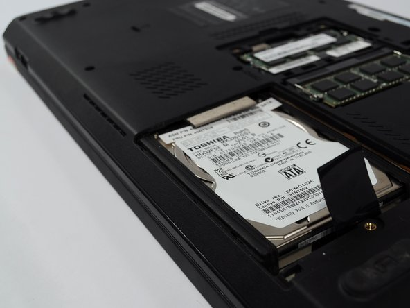 Pull the black tab that is attached to the hard drive up and away from the laptop.