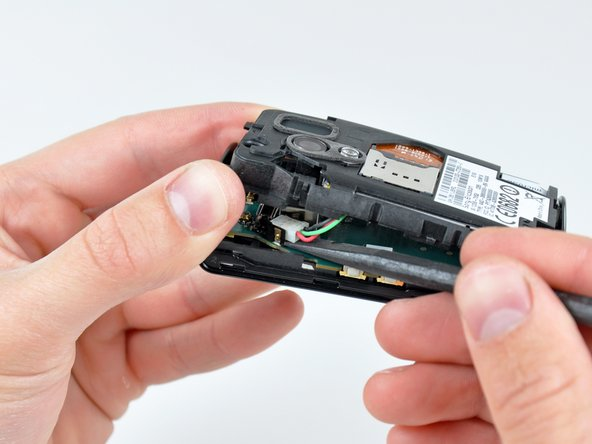 Image 2/3: Pry up the SIM card socket connector and remove the rear inner case from the the logic board.