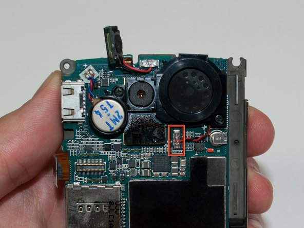 With the iPod opening tool, unclip the red and black wires connecting the speaker to the motherboard.