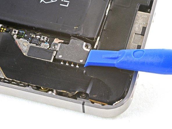 Löse den Akkustecker vorsichtig mit einem Plastiköffnungswerkzeug aus seinem Anschluss auf dem Logic Board. Beginne den Stecker an der Unterseite anzuheben, indem du die Spitze des Werkzeug zwischen Lautsprecherumfassung und Metallabdeckung des Steckers einsetzt.