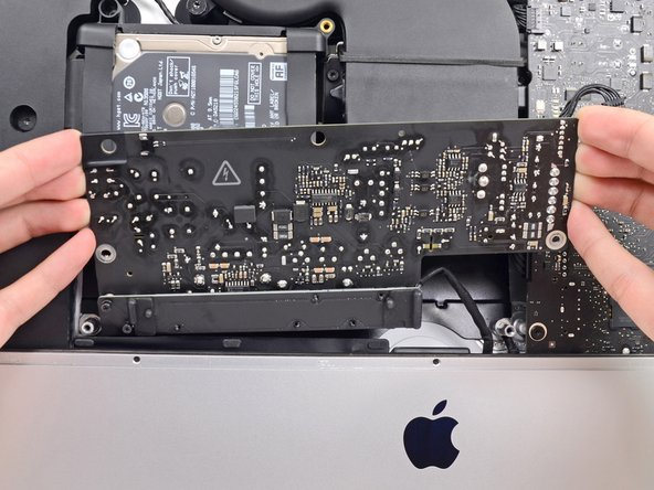 Image 3/3: '''Do not''' try to completely remove the power supply from the iMac yet—it is still connected to the logic board.