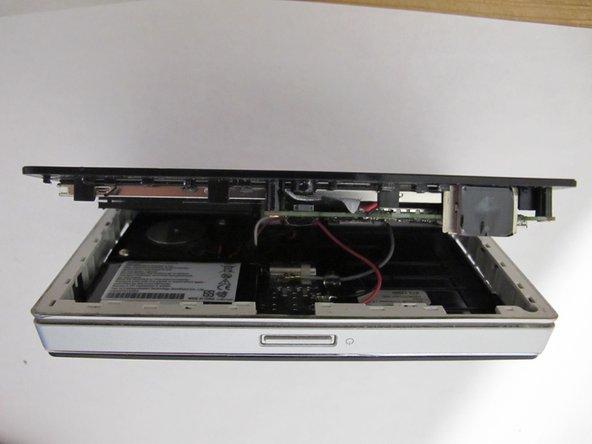 Die Plastikkarte an den unteren Ecken beginnend zwischen Bildschirm und seitlichem Rand durchziehen.